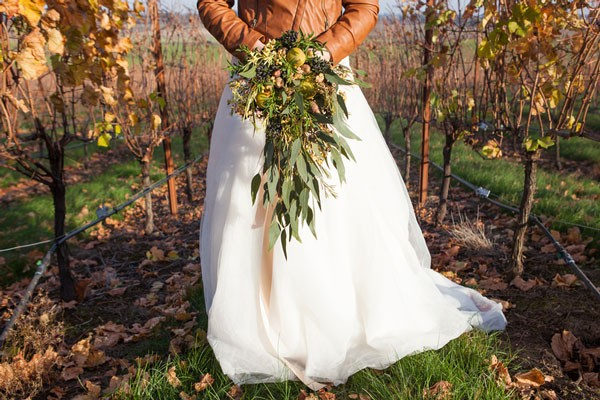 bride with brown leather jacket and cascading bouquet