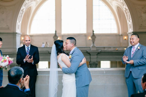 bride and groom kiss after San Francisco City Hall ceremony