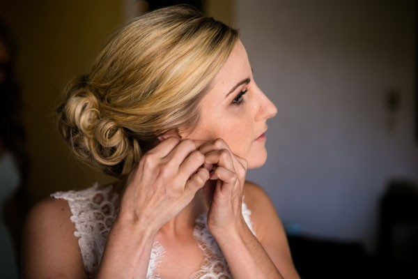 bride with curled updo fasten earrings before wedding