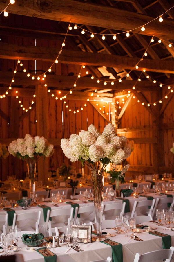tall hydrangea centerpieces and white string lights at barn wedding reception