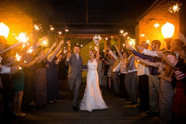 bride and groom exit reception while guests wave sparklers
