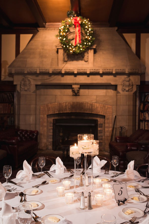 Christmas wreath over stone fireplace at December wedding reception