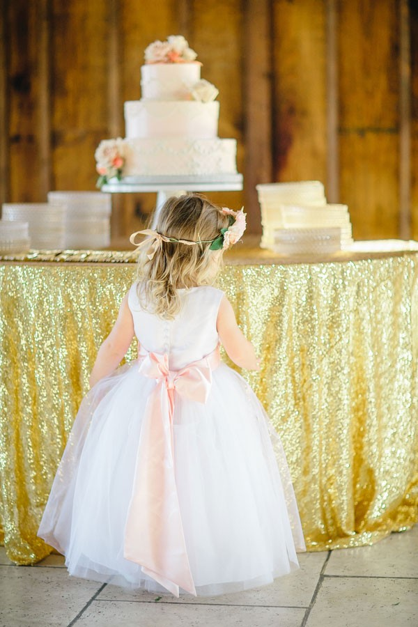 flower girl stares up at wedding cake on table with gold sequined linens