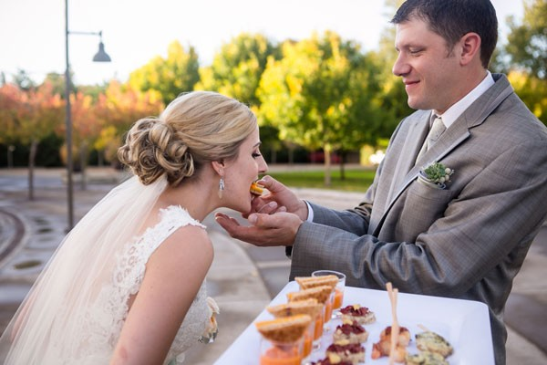 groom feeds bride a sandwich so she does not get her dress dirty