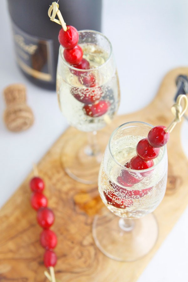 sparkling holiday cocktails with cranberry garnish