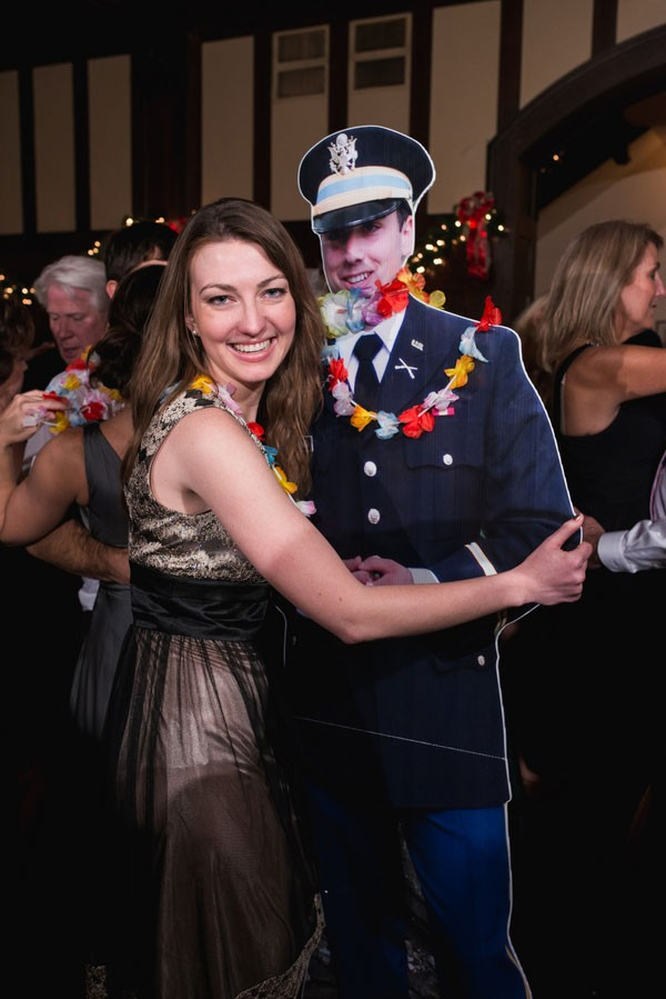 guest dancing with cardboard cutout of relative who couldn't be at wedding
