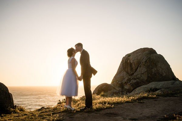 bride in tea length wedding dress and groom kiss on California beach after eloping
