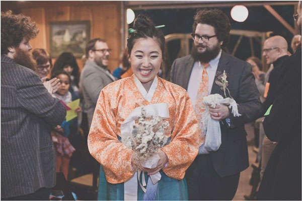 bride with huge smile and simple bouquet followed by groom in orange tie
