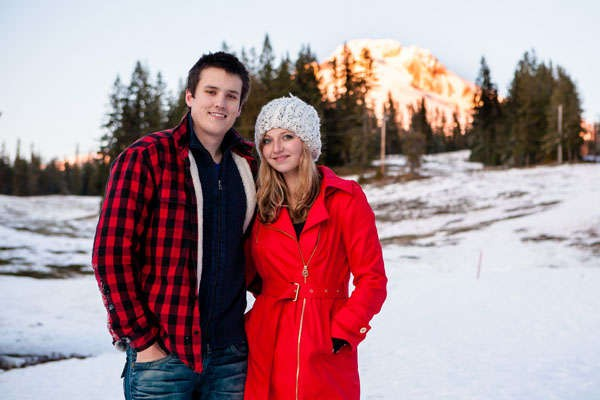 couple standing in snow in red and black