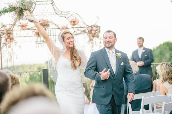 bride and groom trumphantly walk down aisle after wedding ceremony