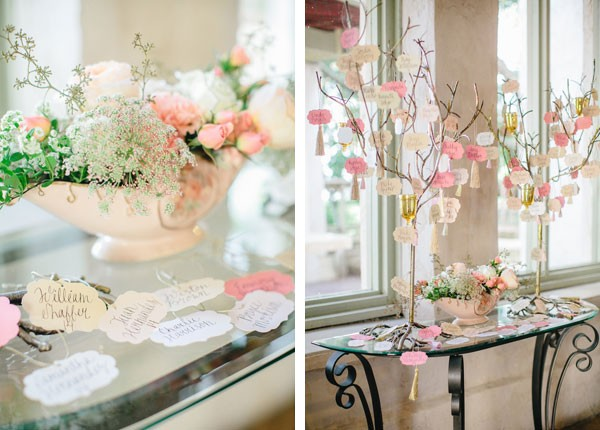 welcome table at wedding reception with pink and white escort cards hanging from branches