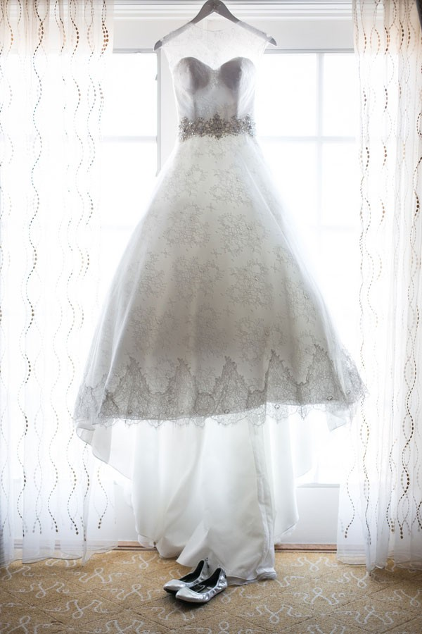 lace princess wedding dress with silver beaded sash hanging in window