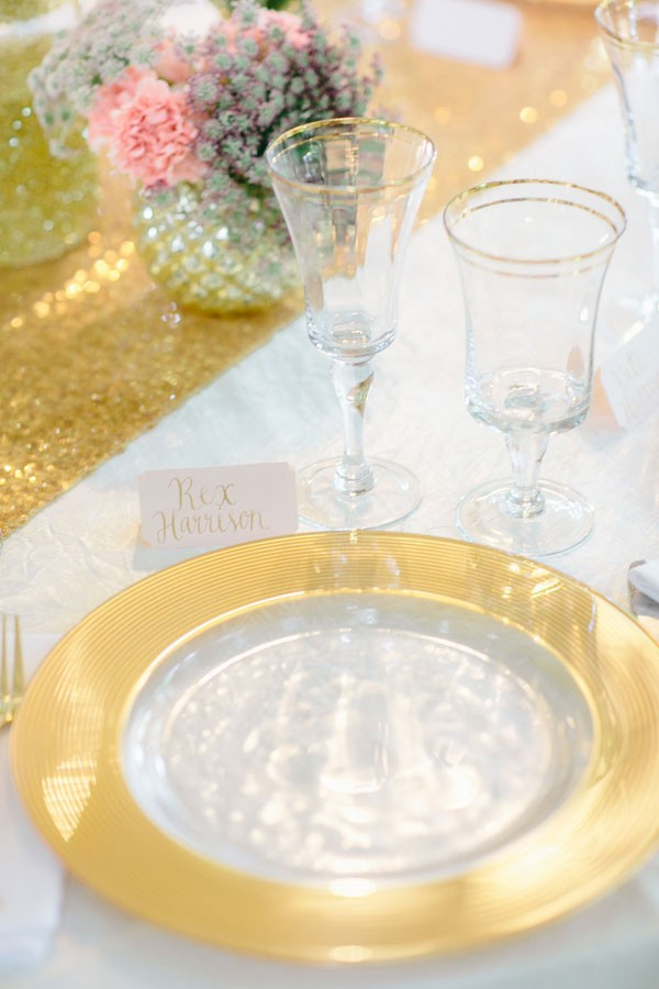 gold place setting with metallic charger and sparkly sequined table runner