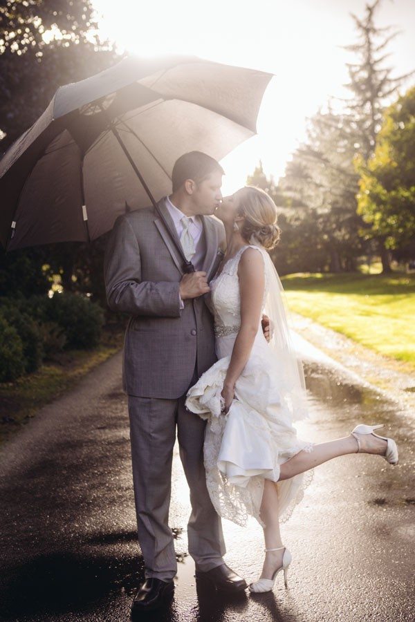 bride and groom kiss under gray umbrella