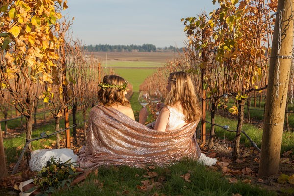 brides drinking wine in vineyard field, wrapped up in sequined blanket