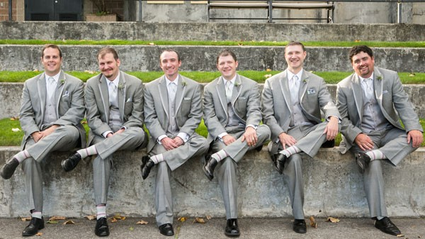 groom and groomsmen sitting in gray suits with pale, striped socks