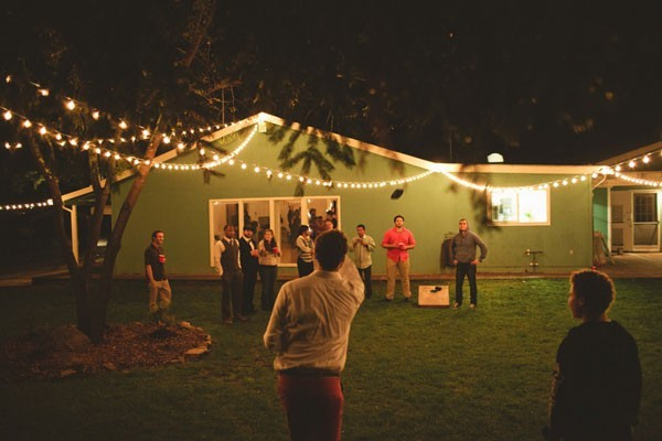 reception guests playing lawn games under string lights