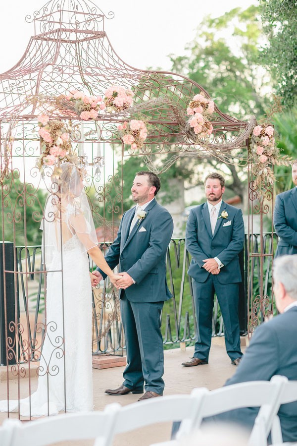 wedding ceremony under arch decorated with pink flowers