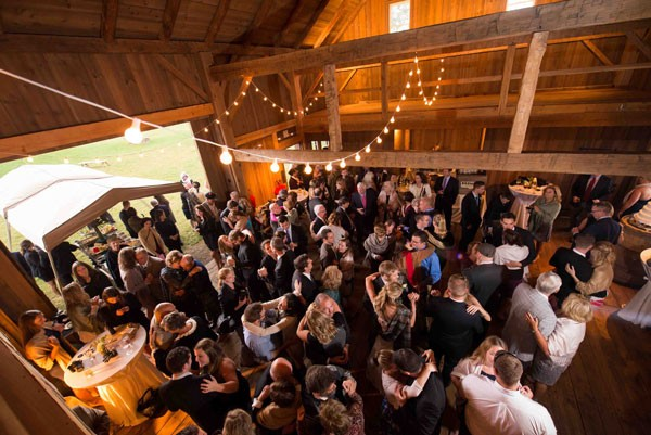 guests dance inside barn at farm wedding under string lights
