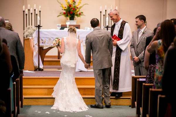 bride in fit and flare gown walks up altar steps with groom and priest
