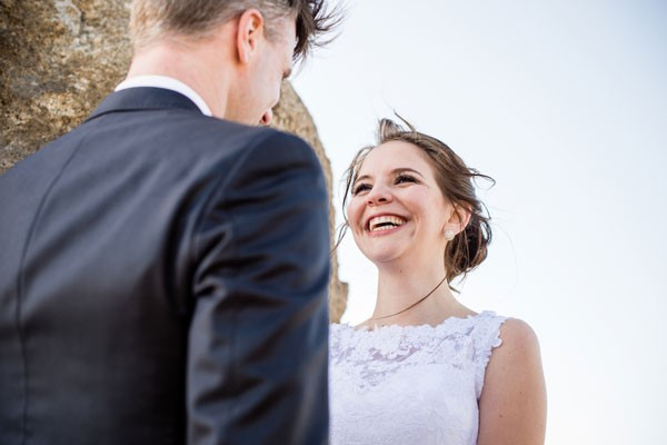 bride in lace dress smiles up at groom during elopement