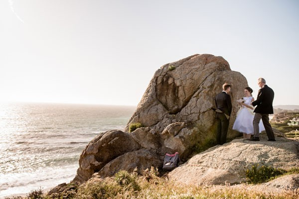 bride and groom get married in front of boulder on California coast
