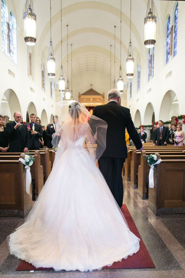bride with long veil and father walk down aisle