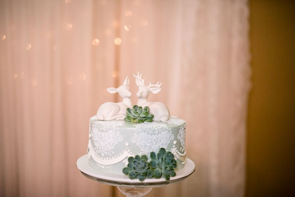 small wedding cake with deer toppers and succulents as decoration