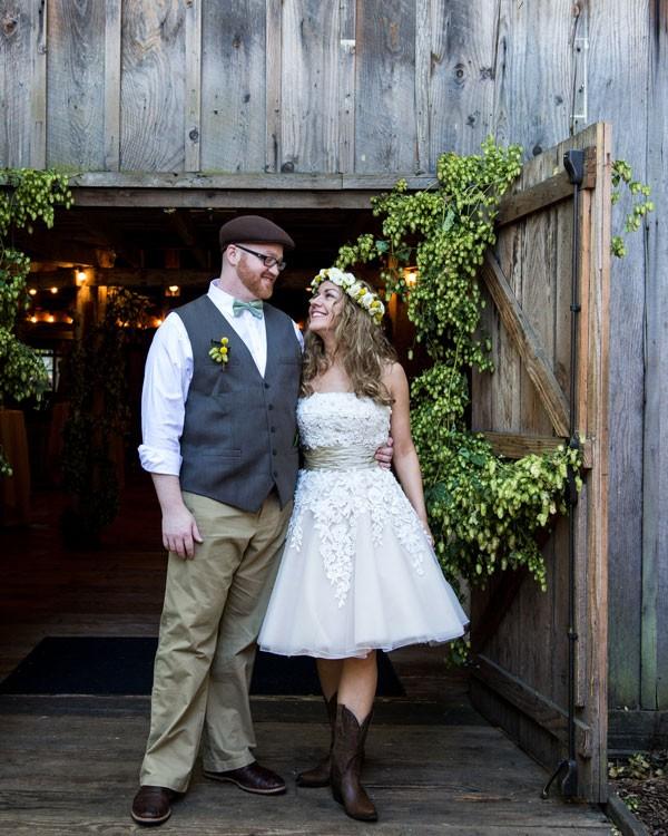 boho bride and groom standing by barn door