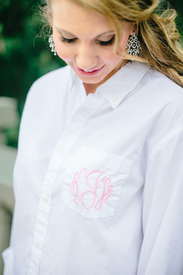 bride getting ready in white Oxford shirt with pink monogram