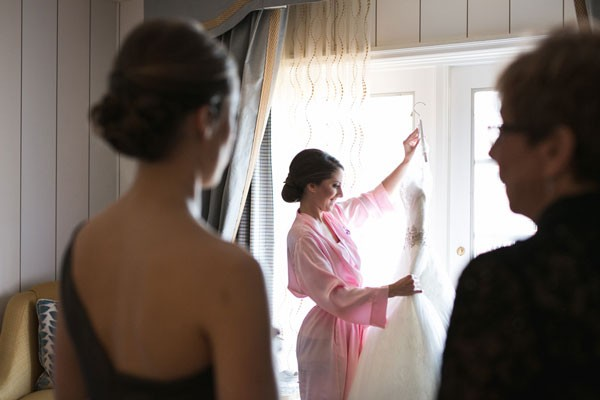 bride in pink satin robe  smiling at wedding dress before getting ready