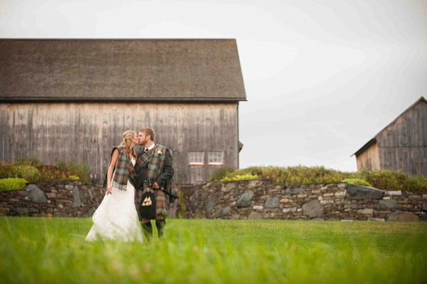 bride and groom in Scottish attire in field in front of barn
