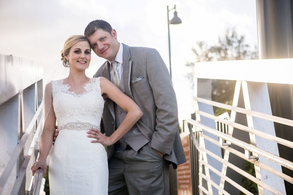 bride and groom lean against white railing at marina