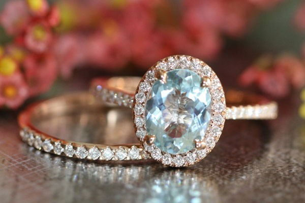 round and light aquamarine engagement ring with band of diamonds
