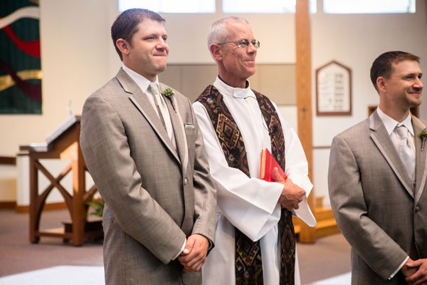 groom and priest wait for bride at end of aisle at altar