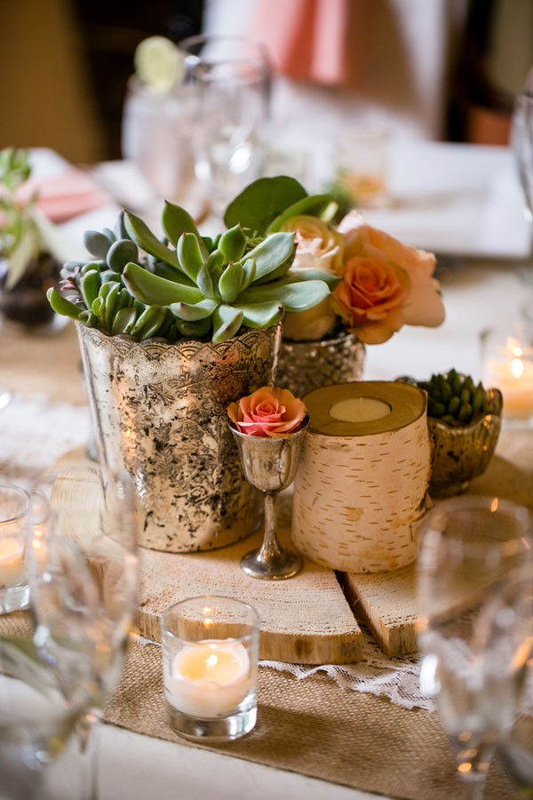 succulents and peach roses in centerpiece with tree trunk-inspired candle holder