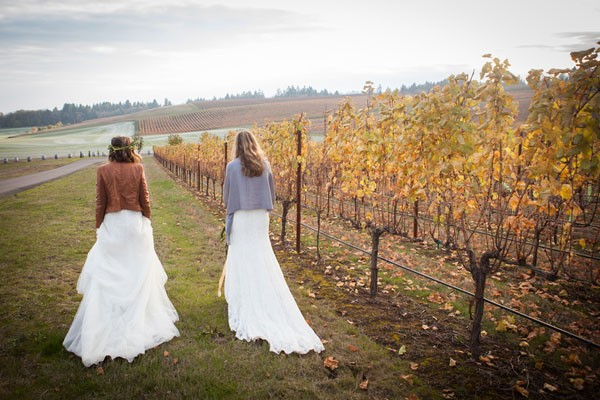 brides walking around vineyard wearing pashmina and leather jacket toppers