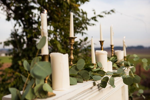 candles and ivy on top of outdoor faux mantel