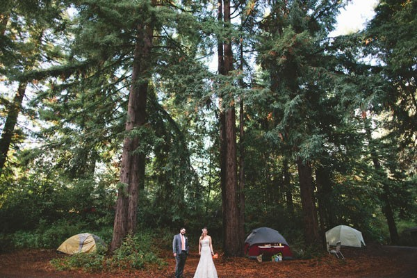 bride and groom by tents at camping wedding