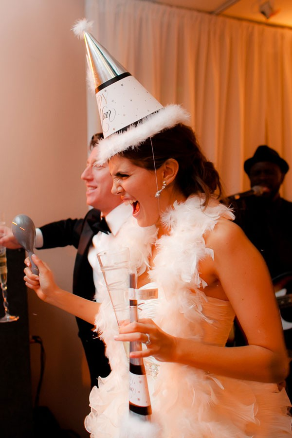 bride on NYE with party hat and white feathered boa