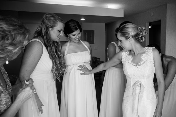 bride puts hand on bridesmaid's pregnant stomach