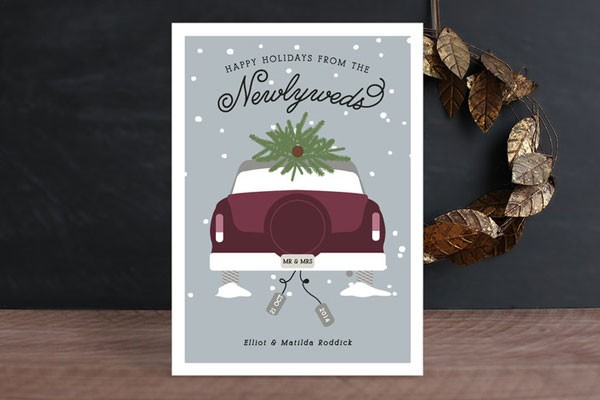 newlyweds Christmas card with purple sedan carrying tree in snow