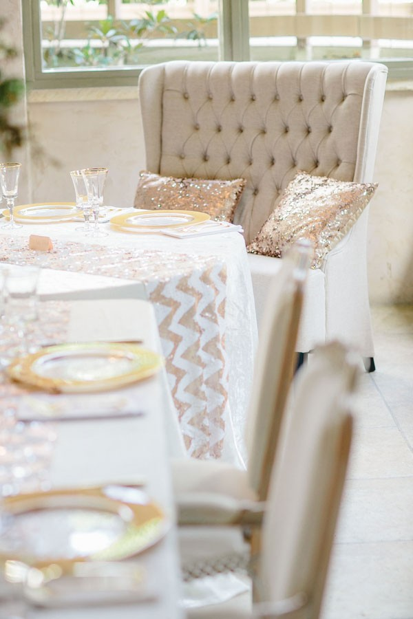 table for bride and groom decked out in chevron patterned sparkly table runner and loveseat with pillows