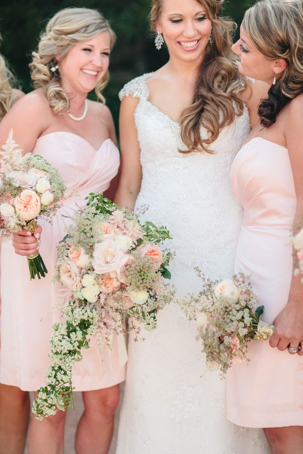 bridesmaid in pale pink dresses with peony and rose bouquets laughing with bride