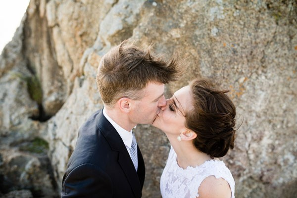 bride and groom kiss in front of boulder at beach elopement