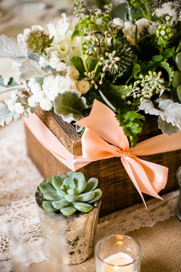 succulents and flowers in wooden box wrapped with peach bow on top of lace doily