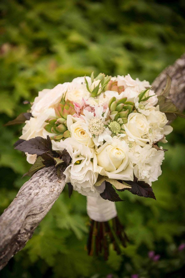 wedding bouquet with white roses resting against fence