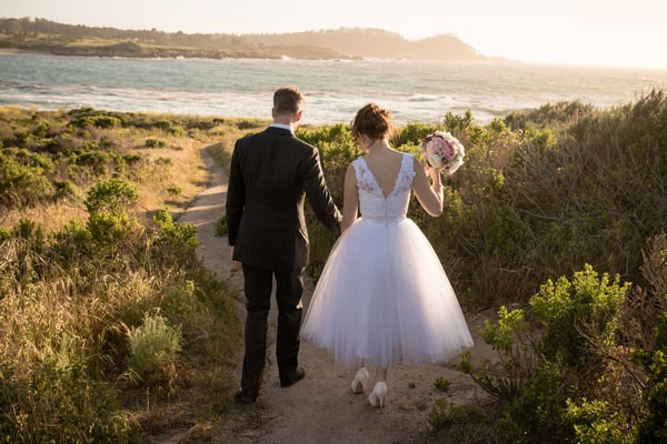 bride and groom walking on beach in central California
