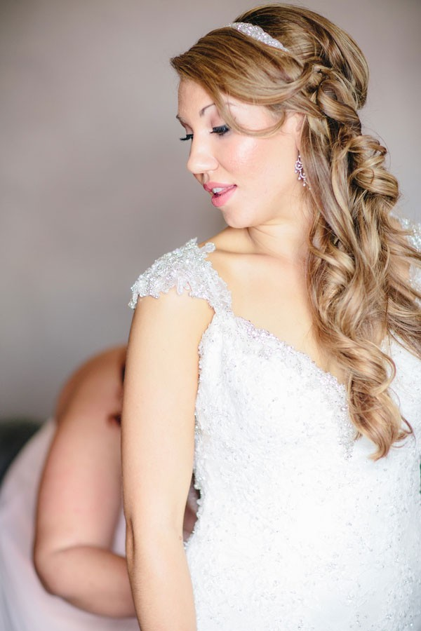 bride with long wavy hair putting wedding dress on
