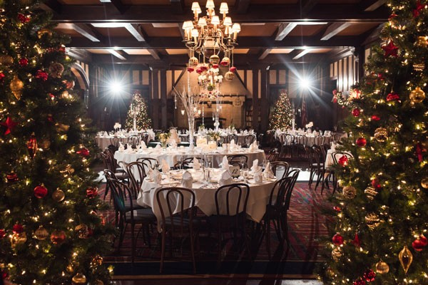 reception venue decrated with Christmas trees and ornament centerpieces